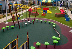 Playground for children with synthetic grass surrounding the play equipment.