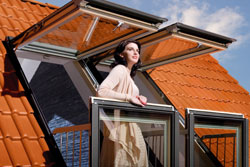 Woman standing on small balcony with open window