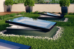 Rooftop window surrounded by grass with planters in the background